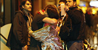 People hug each other before being evacuated by bus, near the Bataclan concert hall in central Paris