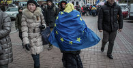 A woman is walking with the EU flag on her back